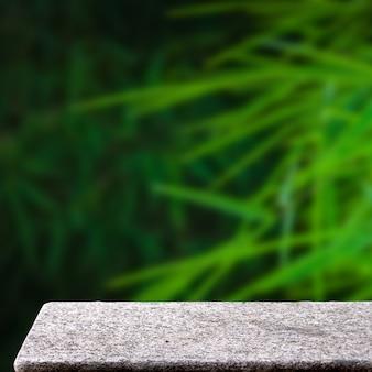 Tavolo di pietra vuoto in foglie di bambù verde all'aperto sfondo di display quadrato di luce solare naturale