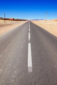 Strada diritta vuota attraverso il deserto