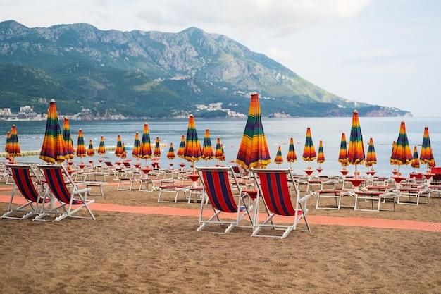 Sedie a sdraio vuote senza persone sotto l'ombrellone arcobaleno sulla spiaggia di ciottoli in riva al mare