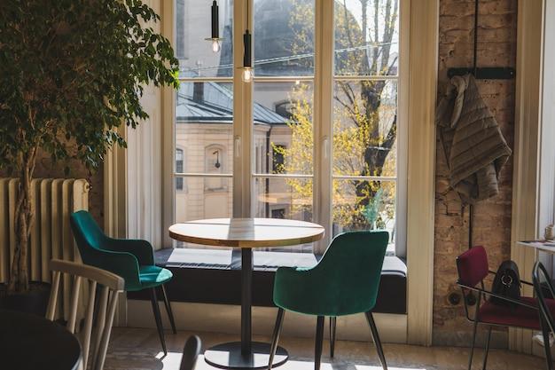 Tavola vuota in caffè vicino allo spazio della copia della finestra all'interno dell'interno