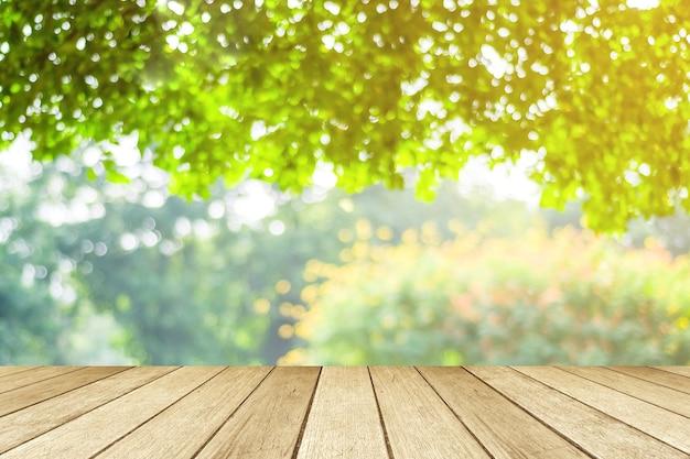 Tavola vuota, legno di prospettiva sopra l'albero della sfuocatura con il fondo del bokeh