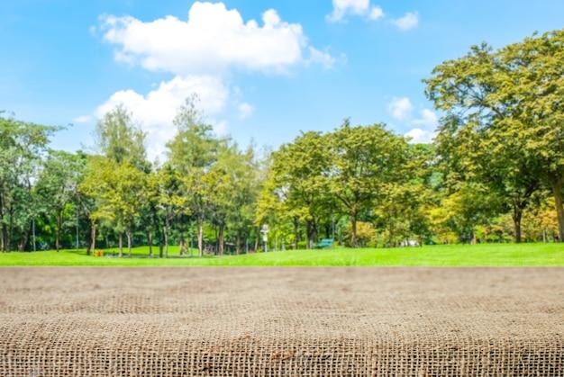 Tavola vuota e tovaglia sacco su sfocatura sfondo parco
