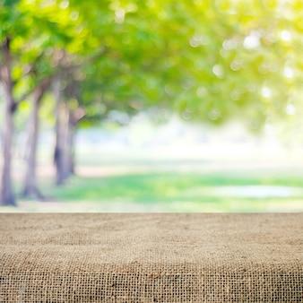 Tavola e tovaglia vuote del sacco sopra l'albero della sfuocatura con il fondo del bokeh, per il montaggio dell'esposizione del prodotto