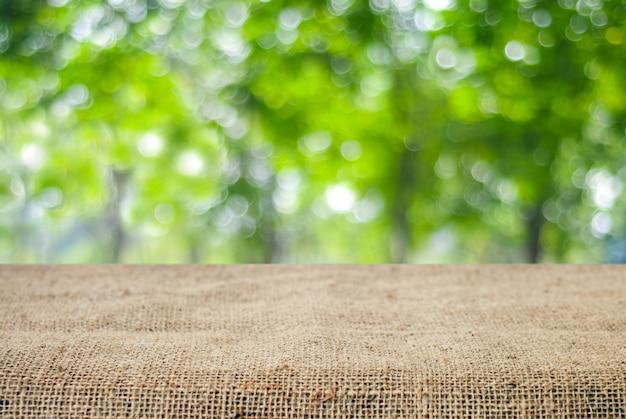 Tavola e tovaglia vuote del sacco sopra l'albero della sfuocatura con il fondo del bokeh