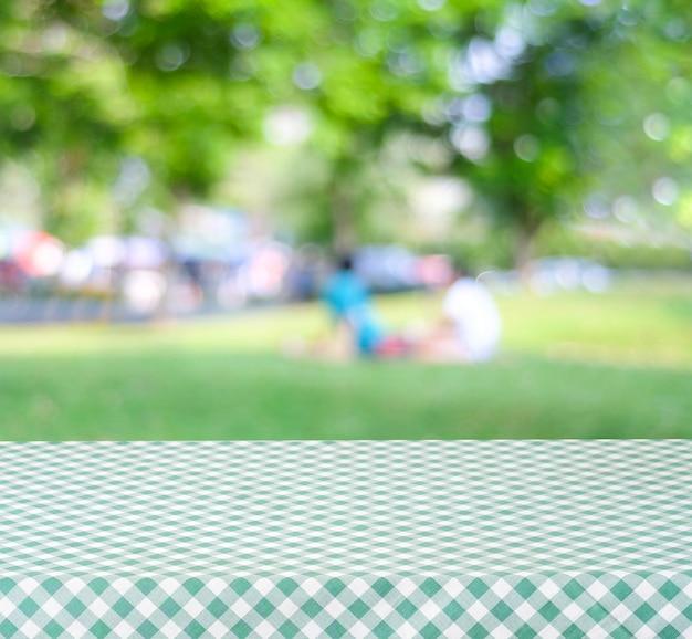 La tavola vuota con la tovaglia verde sopra il parco della sfuocatura con la gente ed il fondo del bokeh, alimento e prodotto visualizzano il montaggio