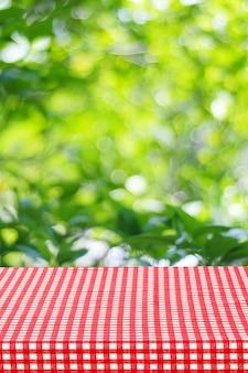 Tavola vuota con tovaglia rossa sopra sfocatura giardino e bokeh sfondo