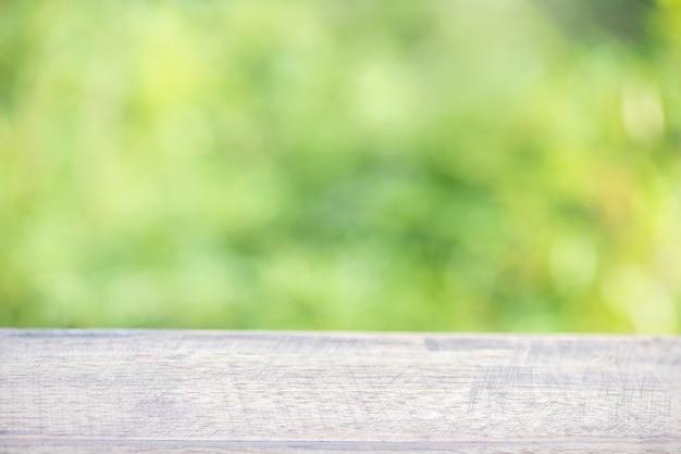 Il legno e il bambù della tavola vuota lasciano il fondo della natura del bokeh.