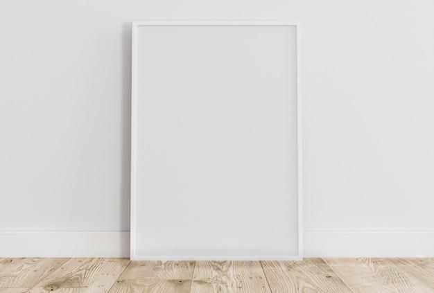 Cornice bianca sottile vuota sul pavimento di legno chiaro con parete bianca dietro di esso.