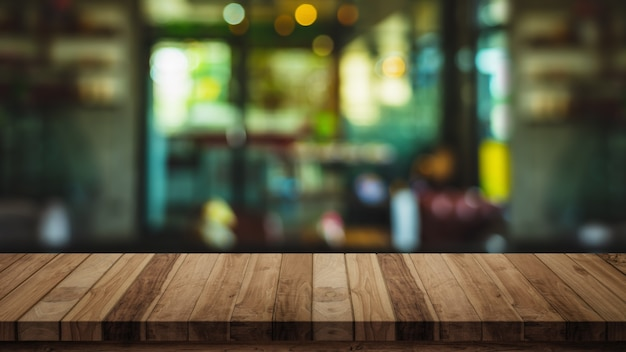 Parte superiore vuota della tavola di legno con la priorità bassa della caffetteria o della caffetteria della sfuocatura