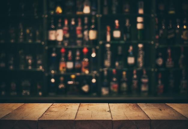 Svuota la parte superiore del tavolo in legno con bancone sfocato e bottiglie