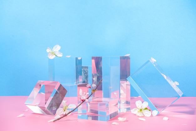 Piedistalli vuoti in vetro trasparente podi per riprese di soggetti, mock up per un photoset, su uno sfondo blu rosa brillante con fiori di ciliegio sakura primaverili