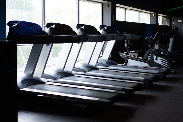 Tapis roulant vuoto in piedi palestra vicino alla grande finestra nessuno sport fitness concetto di stile di vita sano