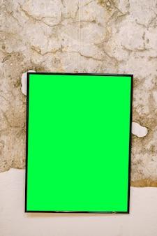 Vuoto dipinto verticale in cornice nera sulla superficie del muro di pietra