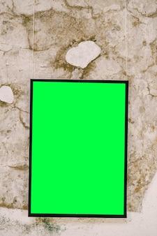 Vuoto dipinto verticale in cornice nera sul muro di pietra