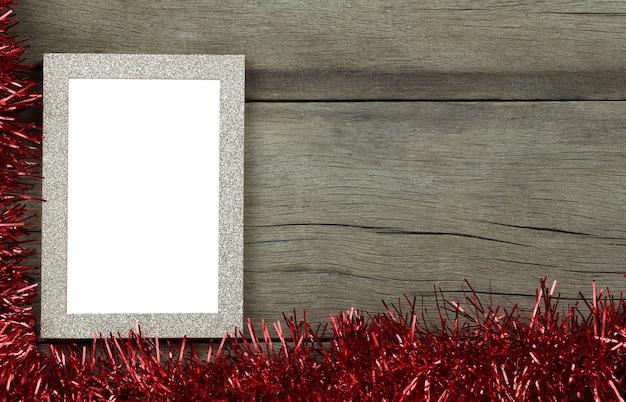 Cornice per foto vintage vuota su pavimento in legno e nappe rosse per decorazioni di natale e capodanno
