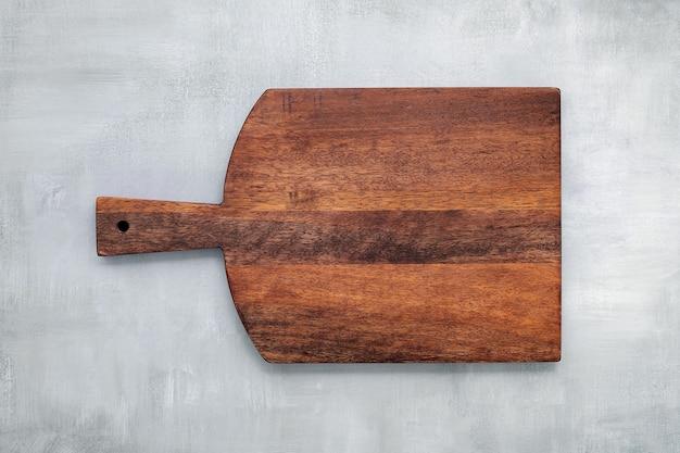 Tagliere di legno vintage vuoto impostato su sfondo di cemento con spazio di copia.