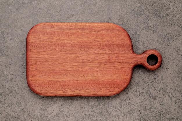 Tagliere di legno vintage vuoto impostato su sfondo di cemento scuro con spazio di copia.