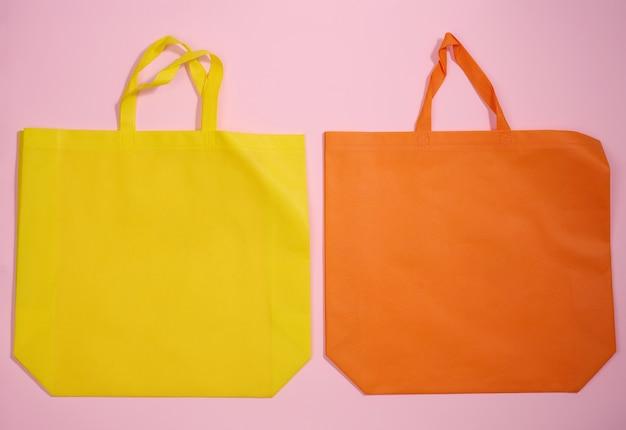 Borsa tote vuota in tela di viscosa ecologica per il marchio su sfondo rosa. borsa riutilizzabile trasparente per la spesa, mock up. lay piatto