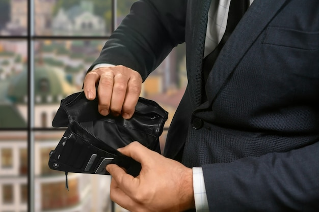Portafoglio vuoto nelle mani dell'uomo d'affari. portafoglio vuoto su sfondo urbano. in attesa di stipendio. situazione veramente triste.
