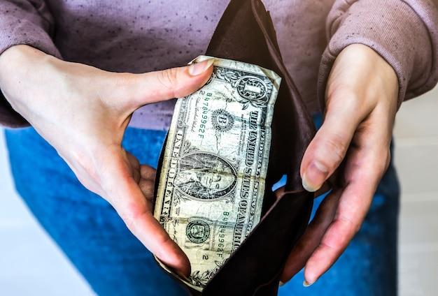 Portafoglio vuoto con solo un dollaro. niente soldi in borsa. crisi economica, povertà, concetto di disoccupazione. conseguenze dell'isolamento delle persone con coronavirus durante la quarantena. tassi di inflazione. crescita dei prezzi.