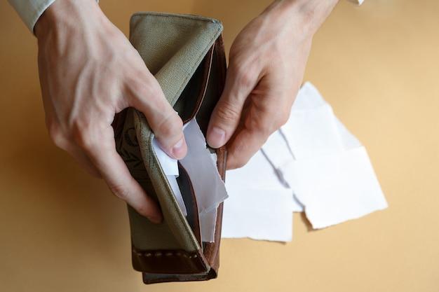 Portafoglio vuoto con carta nelle mani di un uomo su uno sfondo semplice