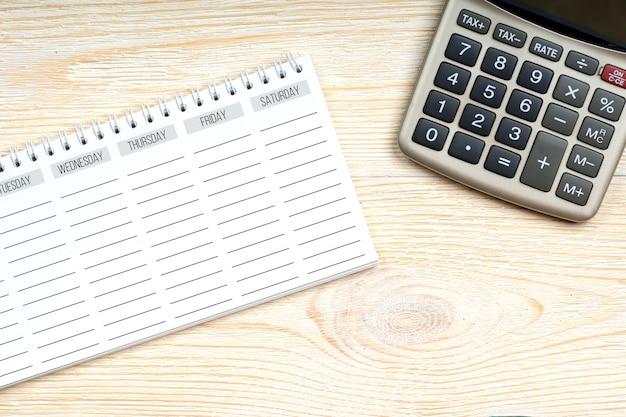 Pianificatore di settimana vuota con il calcolatore sulla tavola dell'ufficio, concetto del posto di lavoro