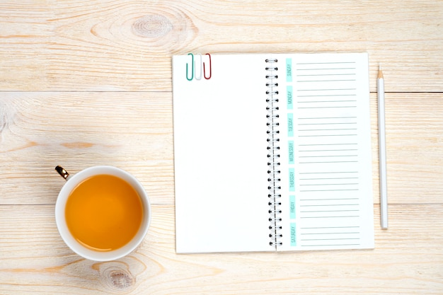 Pianificatore di settimana vuota con la matita sulla tavola bianca, concetto della gestione di tempo