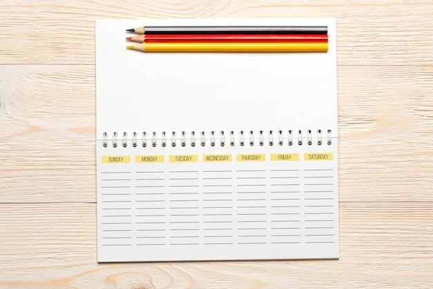 Pianificatore di settimana vuota con le matite sulla tavola bianca, concetto del posto di lavoro