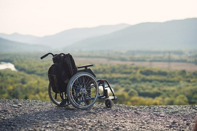 Sedia a rotelle vuota sulle montagne al tramonto. concetto di viaggio di persone con disabilità.