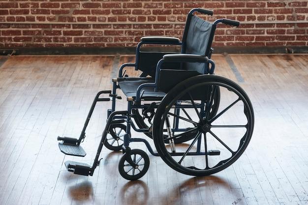 Sedia a rotelle vuota su un pavimento di legno