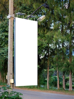 Bandiera in bianco bianca vuota sul palo elettrico per la pubblicità accanto alla strada vicino all'albero e al giardino verde