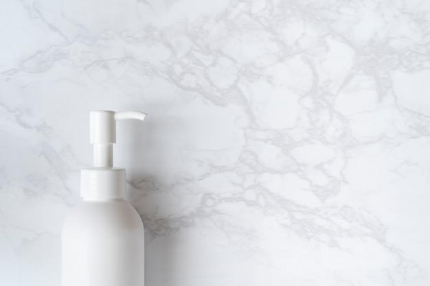 Una bottiglia bianca vuota posta su un tavolo di marmo