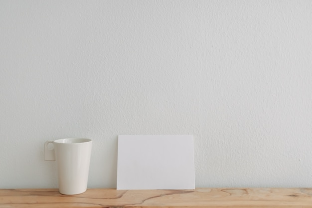 Il modello vuoto della carta bianca si appoggia su una tazza da tè con la parete bianca