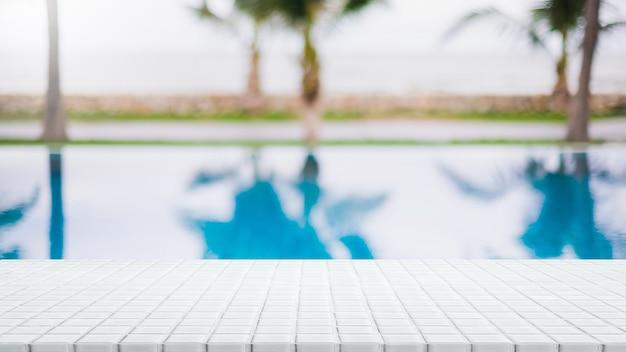 Piano d'appoggio in mosaico ceramico bianco vuoto e piscina sfocata nella località tropicale