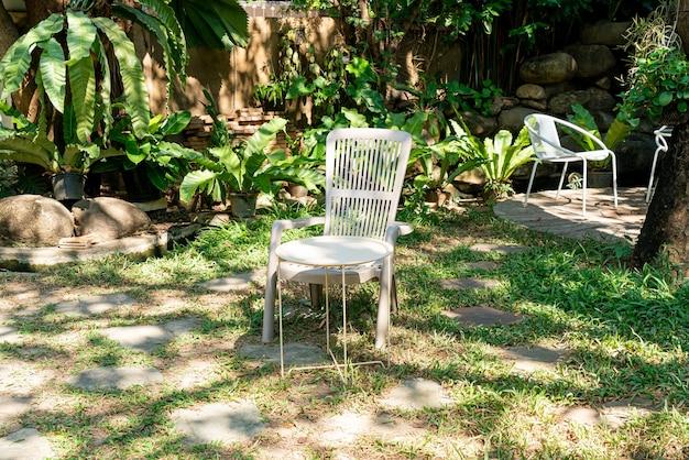 Sedia bianca vuota in giardino