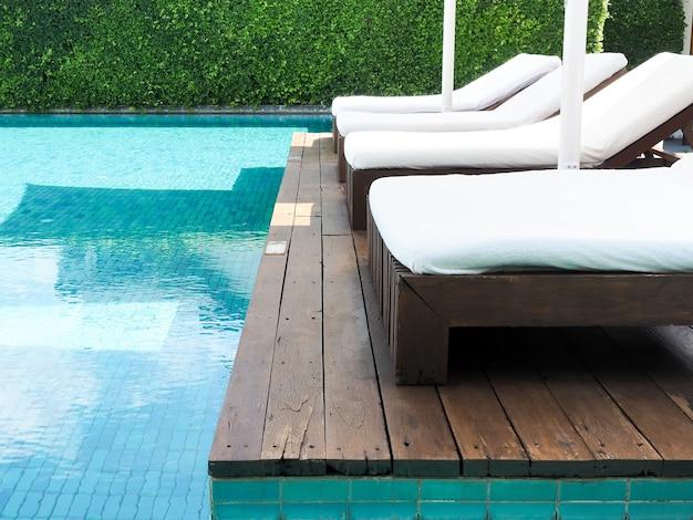 Lettini puliti bianchi vuoti sulla terrazza in legno vicino alla piscina in giornata di sole in estate.