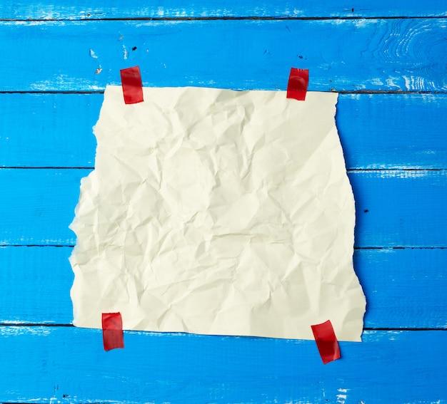 Foglio di carta sgualcito bianco vuoto incollato con pezzi di carta appiccicosi rossi