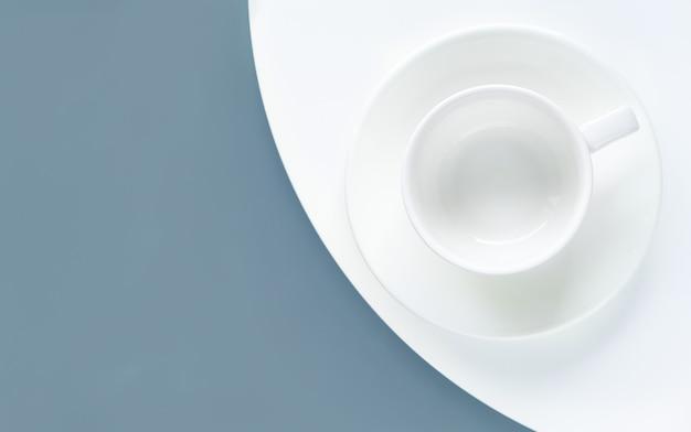 Tazza bianca vuota su sfondo blu e bianco. lay piatto, mock up