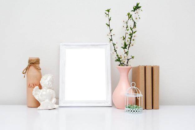 Cornice bianca vuota con un vaso e libri sul tavolo. mock-up di primavera per il tuo testo.