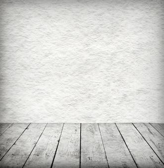 Interno bianco vuoto della stanza d'epoca senza soffitto dalla parete di pietra grigia del grunge e dal vecchio pavimento in legno.