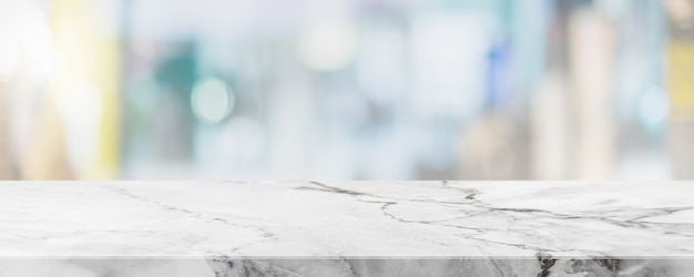 Piano del tavolo vuoto in pietra di marmo bianco e sfocatura della finestra interna del caffè e del ristorante banner mock up sfondo astratto - può essere utilizzato per visualizzare o montare i tuoi prodotti