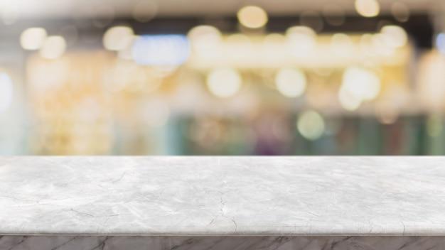 Piano d'appoggio di pietra di marmo bianco vuoto e caffetteria e ristorante interni della finestra di vetro della sfuocatura.