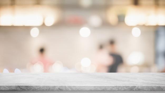 Svuoti il piano d'appoggio di pietra di marmo bianco e il caffè interno della finestra di vetro della sfocatura