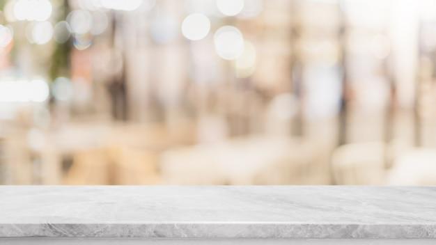 Piano d'appoggio di pietra di marmo bianco vuoto e fondo della parete della finestra di vetro della sfuocatura
