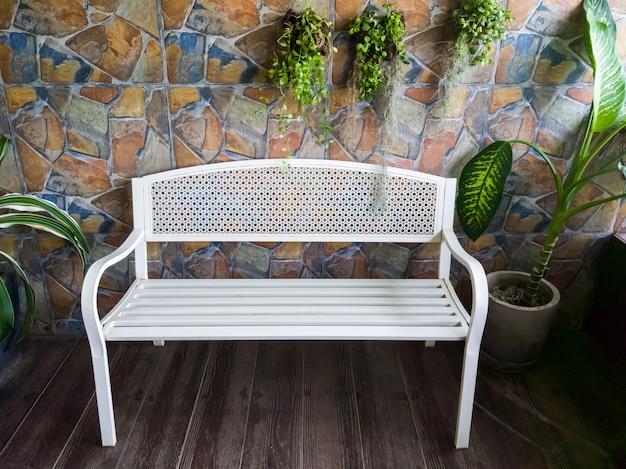 La panchina vuota in metallo bianco in stile retrò vicino alla terrazza in legno e decorata con la pianta.