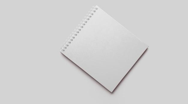 Mockup di quaderno bianco vuoto con ombre morbide su sfondo di cemento grigio neutro.