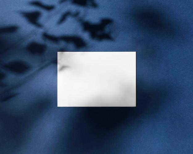 Carta bianca vuota a5 mock up con foglie ombre su sfondo blu classic blue pantone color flat lay top view identità del marchio