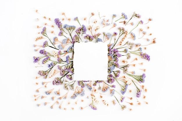 Libro bianco vuoto in bianco sul telaio di fiori secchi blu e viola su sfondo bianco. disposizione piatta, vista dall'alto