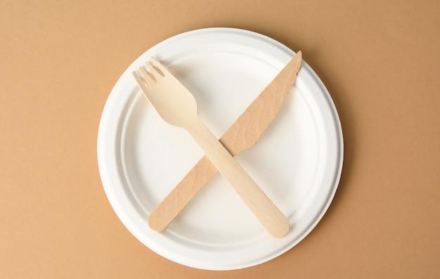 Piatto di carta bianco vuoto e coltello e forchetta di legno, oggetti incrociati, vista dall'alto