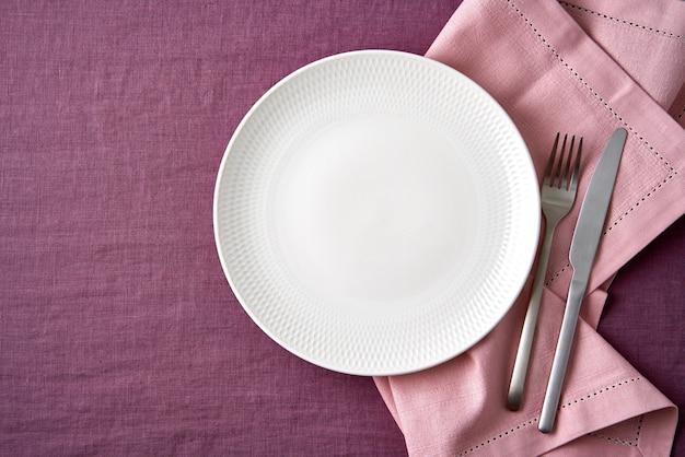 Forchetta e coltello bianchi vuoti del piatto sulla tovaglia di lino rossa luminosa del mirtillo